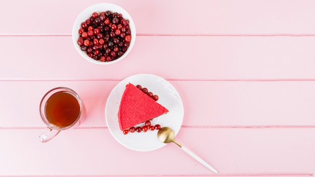 レッドカラントベリーケーキのスライス。ジュースとベリーピンクの木製の背景 無料写真