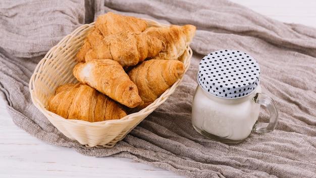 しわくちゃの袋織物のクローズドメイソンジャーで焼きクロワッサンとミルク 無料写真