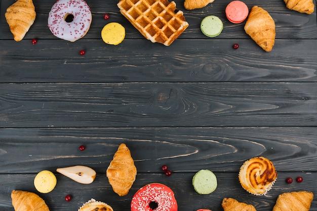 焼きたてのクロワッサン。マカロン;ドーナツと木製の織り目加工の背景にカップケーキ 無料写真