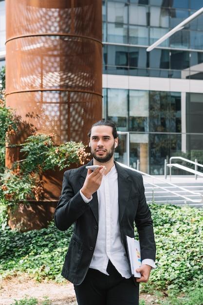 携帯電話を手で押し、拡声器で話している建物の前に立つ 無料写真