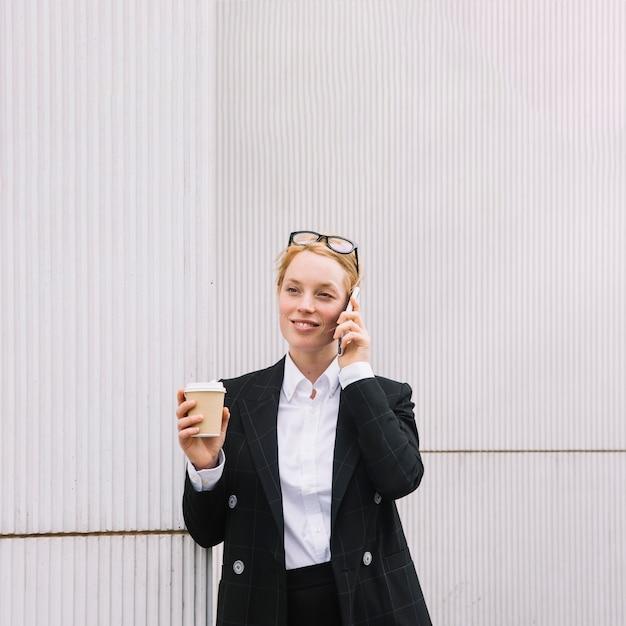持ち帰り用のコーヒーカップを保持している携帯電話で話している笑顔の若い実業家 無料写真