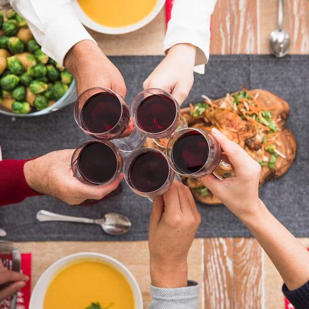 お祝いのテーブルの上にワイングラスを握っている人々 無料写真