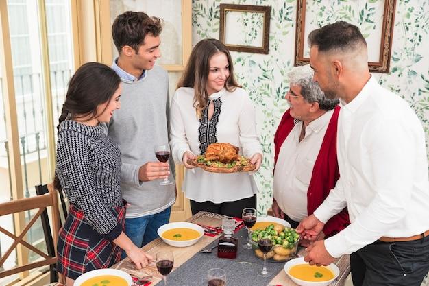 お祝いのテーブルで焼いた鶏を持つ女性 無料写真