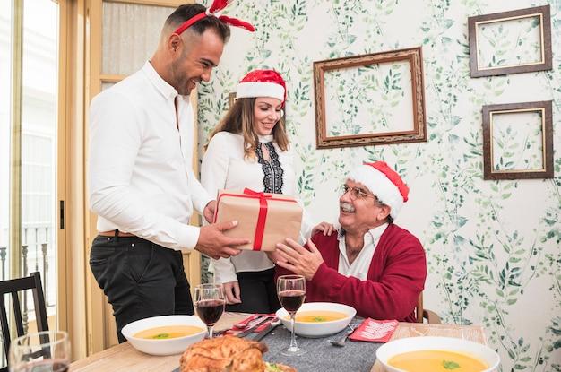 幸せな老人に白いギフトボックスを与える男 無料写真