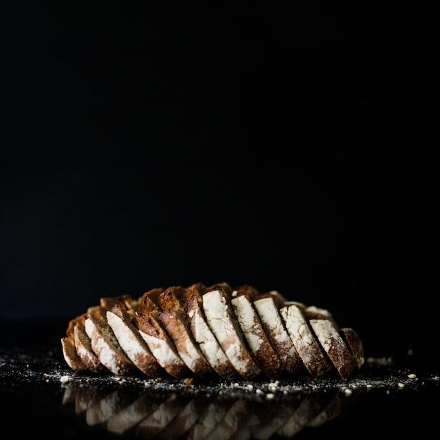 黒の背景に焼きたてのパンのスライス 無料写真