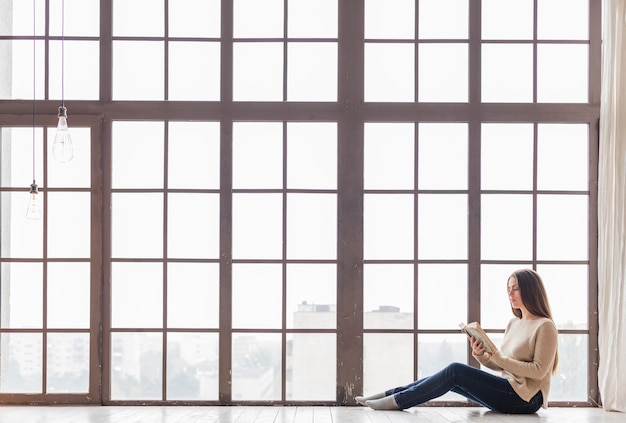 本を読んで窓の近くの床に座っているトング女 無料写真