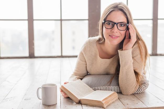 本を持って眼鏡を手で堅木張りの床に横になっている笑顔の若い女性 無料写真