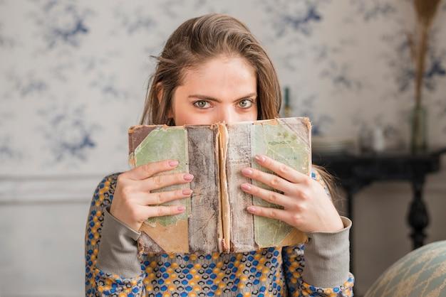 Молодая женщина закрыла рот рваной книгой Бесплатные Фотографии