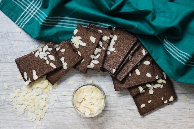 アーモンドスライスとダークチョコレートのスライスの木製の背景の俯瞰 無料写真
