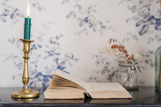 ローソク足ホルダーと壁紙に対して机の上の開いた本の上に火をつけたキャンドル 無料写真