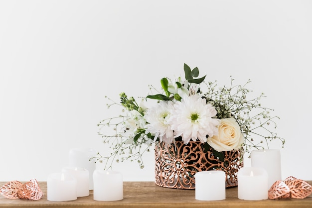 白い背景に対して木製のテーブルの上の白いキャンドルで装飾的な花瓶 無料写真