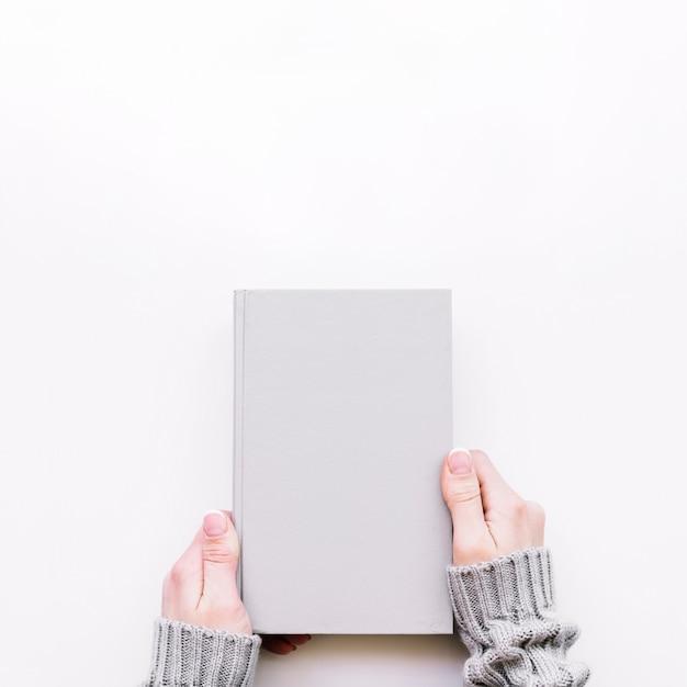 閉じた手帳を手にしている手 無料写真