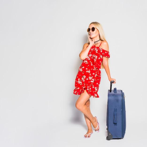 金髪の観光客がスーツケースでポーズ 無料写真