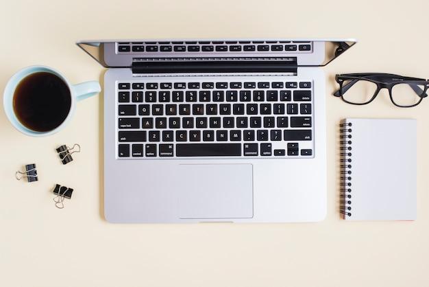 ティーカップペーパークリップ;めがねノートパソコンとベージュの背景にスパイラルノート 無料写真