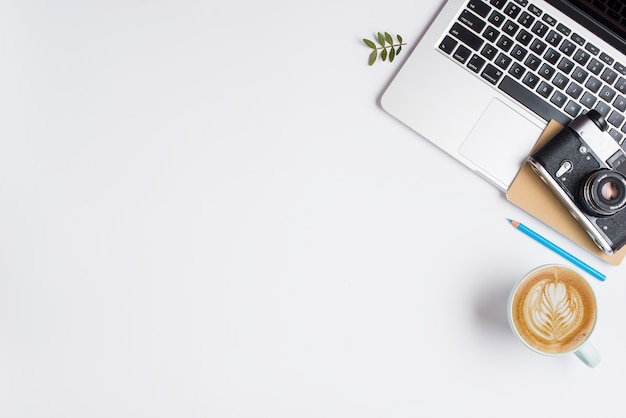 古いカメラ青鉛筆と白い背景の上のカプチーノのカップとラップトップ上のノートブック 無料写真