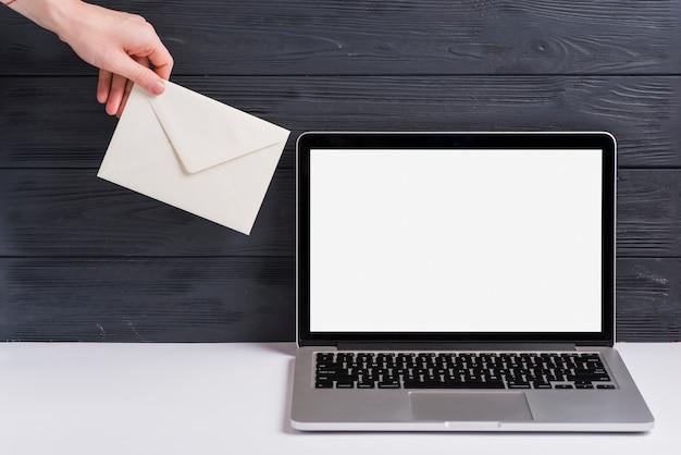 黒い木製の背景に対して机の上のノートパソコンの近く白い封筒を持っている人の手のクローズアップ 無料写真
