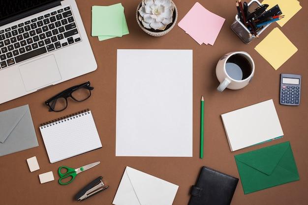 コーヒーカップと茶色のデスクトップ。ラップトップ・事務用品 無料写真