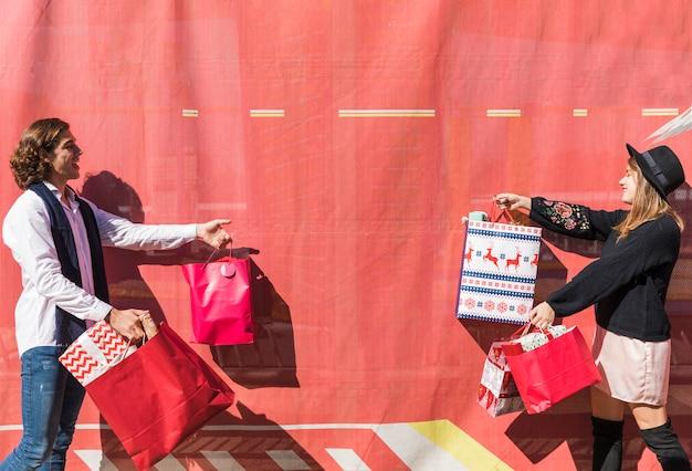 買い物袋を持つ若いカップル 無料写真
