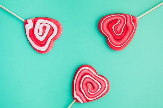 緑色の背景でハート形の赤いキャンディーを旋回します。 無料写真