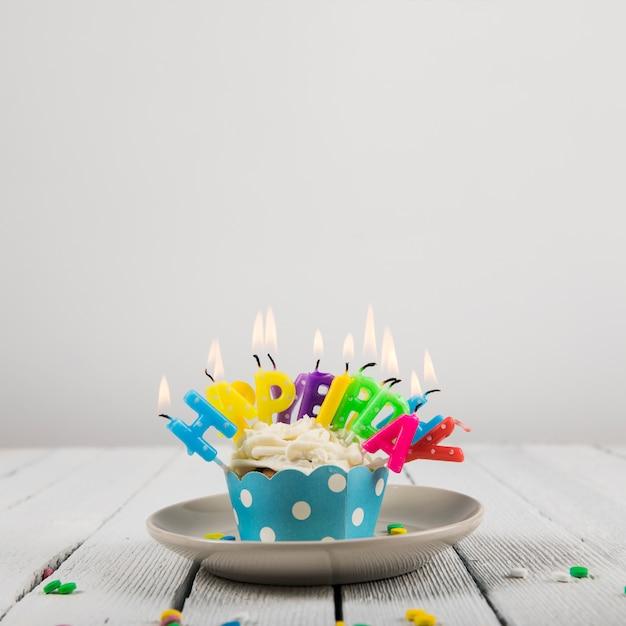 白い背景に対してセラミックプレート上のカップケーキの上の誕生日おめでとう手紙キャンドル 無料写真