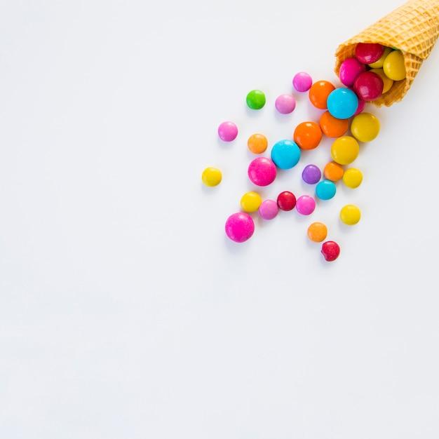 白い背景の上のワッフルコーンからこぼれたカラフルなキャンディー 無料写真