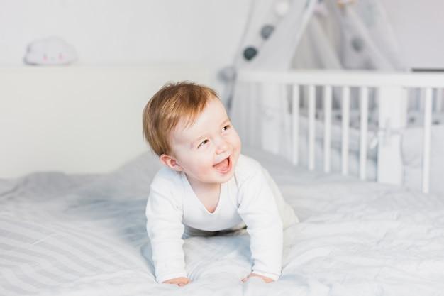 白いベッドでかわいいブロンドの赤ちゃん 無料写真