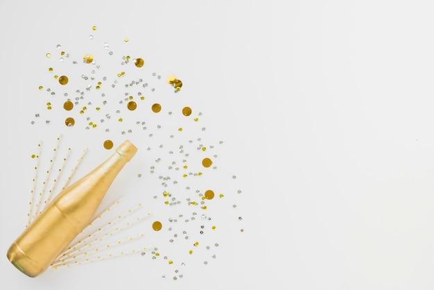 Бутылка напитка и орнамента конфетти и палочки Бесплатные Фотографии