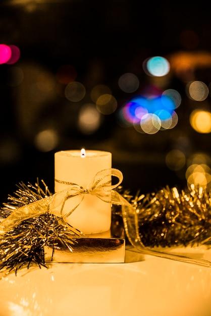 Пылающая свеча с луком и мишурой Бесплатные Фотографии