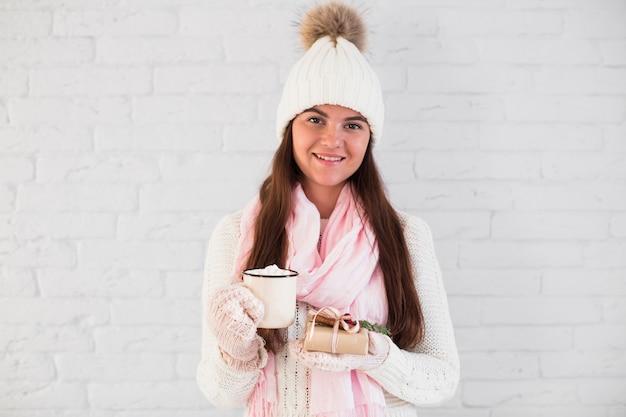 Очаровательная дама в варежках, шапочке и шарфе с кружкой и настоящей коробкой Бесплатные Фотографии