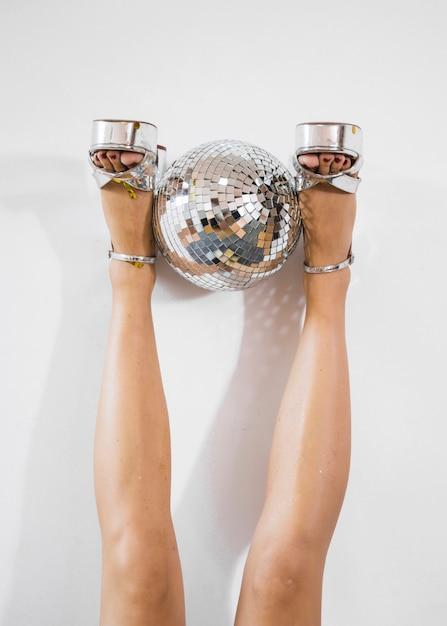 ディスコボールを持っているスリムな女性の足 無料写真