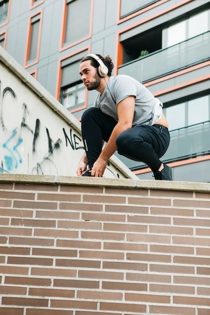 Городской спортсмен, закрепляющий обувь Бесплатные Фотографии