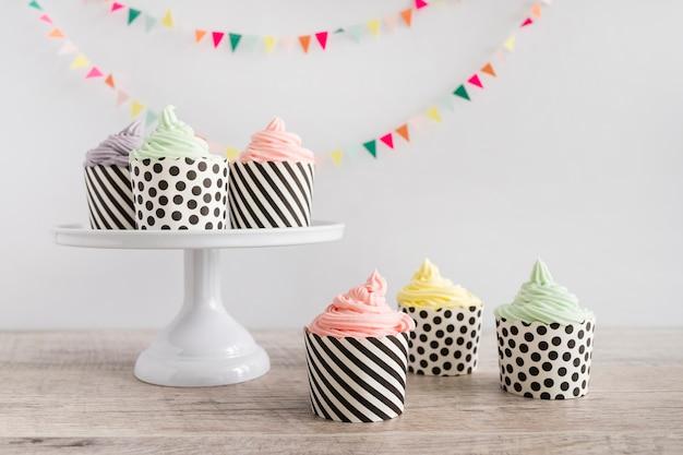 ペナントの前にカップケーキのパステルカラーのバタークリーム 無料写真