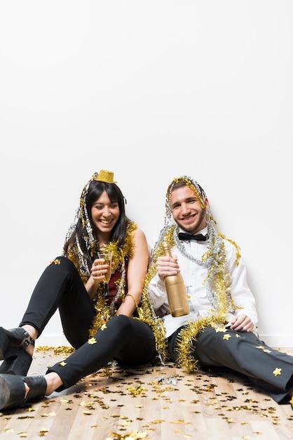 Смеющаяся леди и парень в вечерней одежде и мишура с бутылкой и стаканом на полу Бесплатные Фотографии