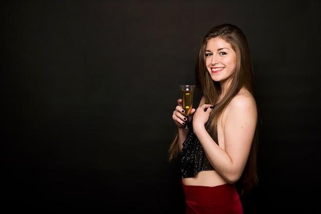 ドリンクのガラスと夕方の布の魅力的な幸せな女性 無料写真