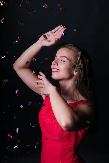 光るスパンコールの下でピンクの踊りをする女性 無料写真