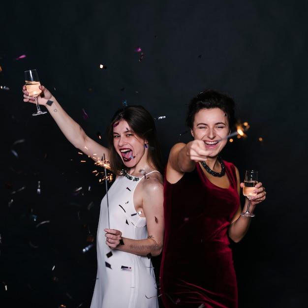 シャンパングラスとスパークラーを持つ幸せな女性 無料写真