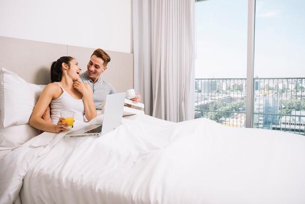 Пара прижимается и смеется в постели утром Бесплатные Фотографии
