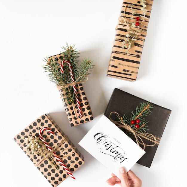 手、クリスマスカード、ギフトボックスの上に 無料写真