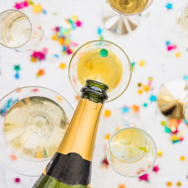 Шампанское, залитое стеклом на белом столе Бесплатные Фотографии