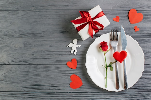 Красная роза с столовыми приборами на белой тарелке Бесплатные Фотографии