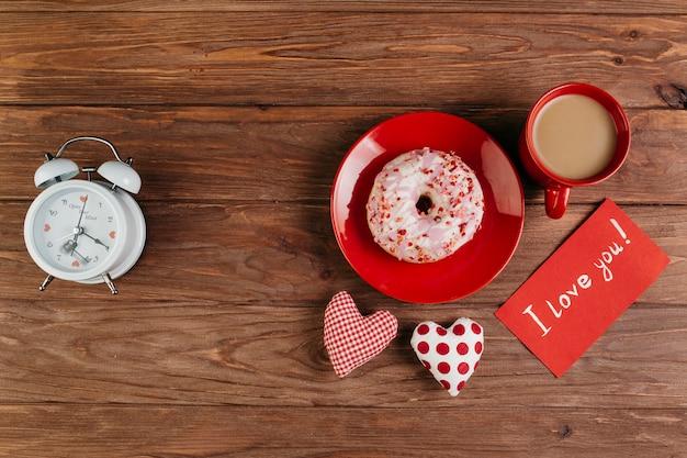 カップとバレンタインデコレーションの間のプレート上のドーナツ 無料写真