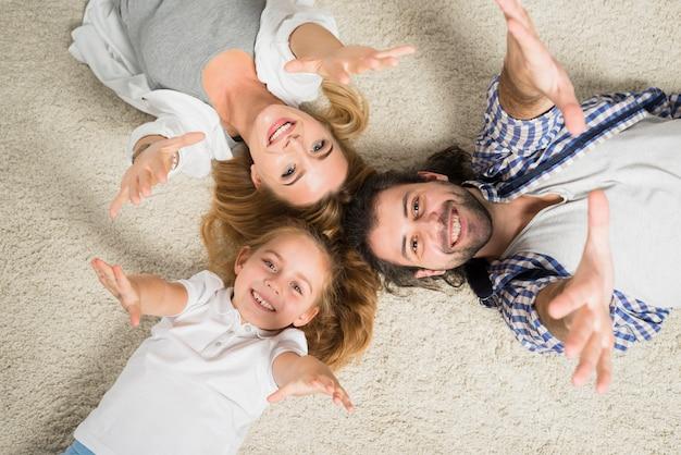 トップビュー家族の肖像画は、カーペットに横たわる 無料写真