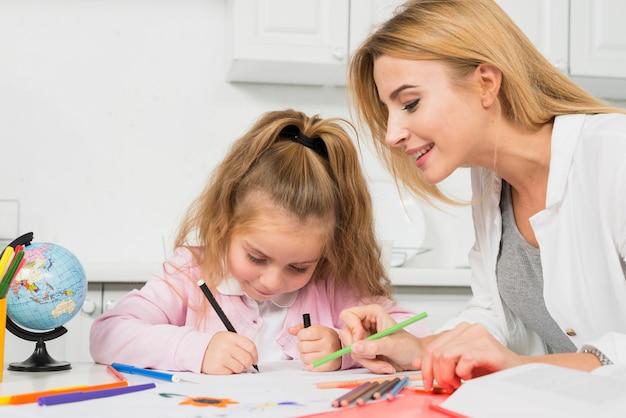 Мать, помогая дочери с домашним заданием Бесплатные Фотографии