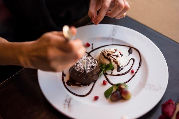 Женщина с вилкой и вкусный свежий шоколадный десерт в ресторане Бесплатные Фотографии