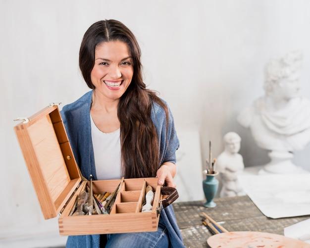 ブラシの木箱を持つ女性アーティスト 無料写真