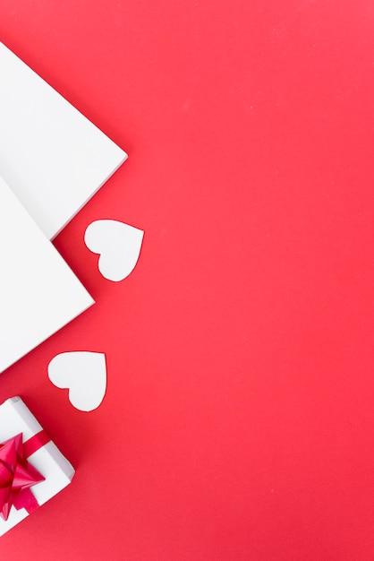 Бумаги с орнаментом сердца и подарочной коробкой Бесплатные Фотографии