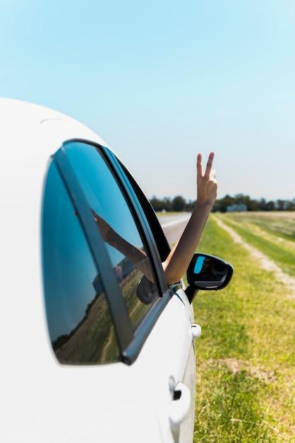 車の窓から平和サインを作る手 無料写真