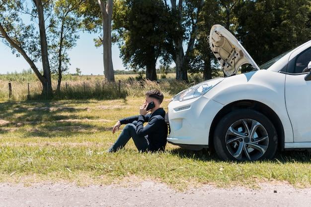 壊れた車の隣に電話する男の子 無料写真