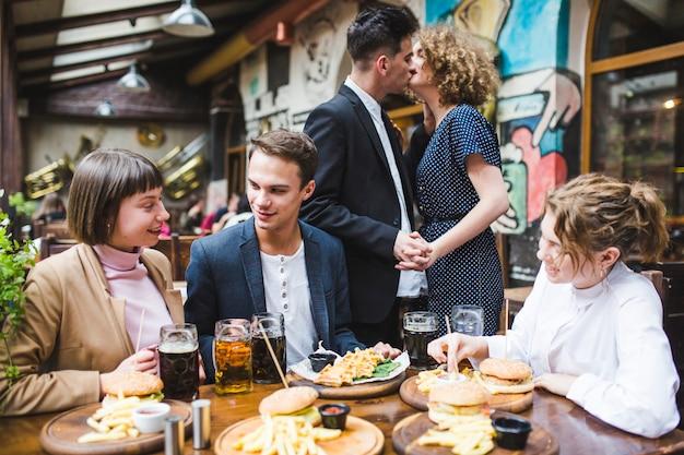 Друзья едят и общаются в ресторане Бесплатные Фотографии