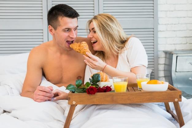 朝食のテーブルの食事の近くのベッドで男性にクロワッサンを与える笑顔の女性 無料写真